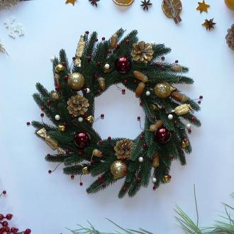 Большой новогодний рождественский хвойный венок с шишками и ягодами.