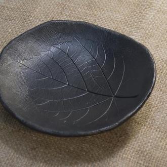 Керамическая тарелка черная с оттиском листа.