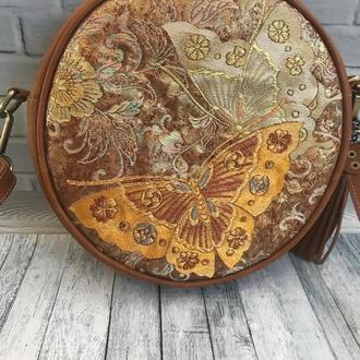 Круглая сумка из натуранльной кожи с вышитым орнаментом в виде бабочки.