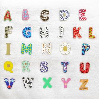 Эмалевые значки в виде букв английского алфавита.
