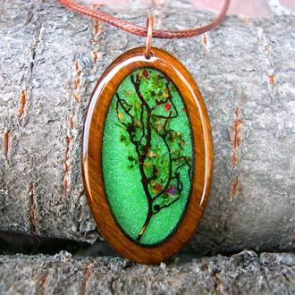 Деревянный кулон с деревом на зеленом фоне
