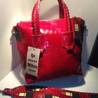 Стильная красная женская кожаная сумка, с декоративными помадами и дополнительной ручкой.