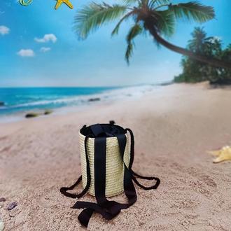 Циліндрична солом'яна сумка через плече, декорована чорними рапсовими стрічками.