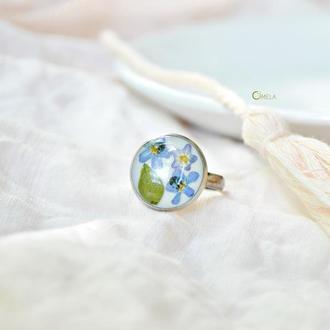 Перстень с незабудками и зелеными листочками акации на белоснежном фоне