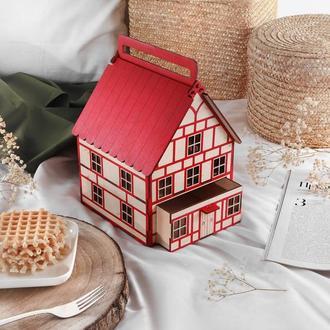 Деревянный домик в баварском стиле. Праздничная упаковка новогодних подарков.
