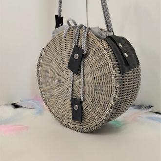 Светло серая круглая плетеная сумка с длинной плетеной ручкой