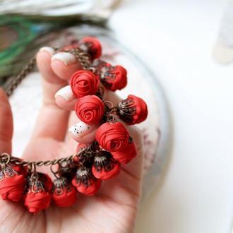 красный браслет с текстильными подвесками в виде розочек