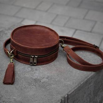 Круглая кожаная сумка с кисточкой