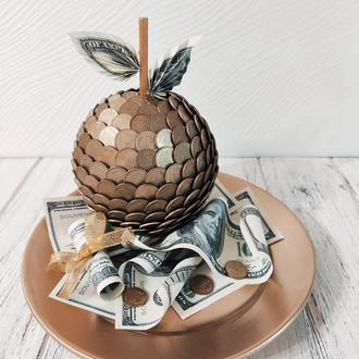 Яблоко из монет на золотой тарелке с долларами