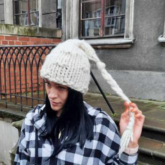 Біла вязана жіноча шапка з косою. Вязана зимова шапочка