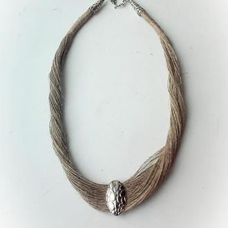 Колье из льняной нити с серебристым медальоном.