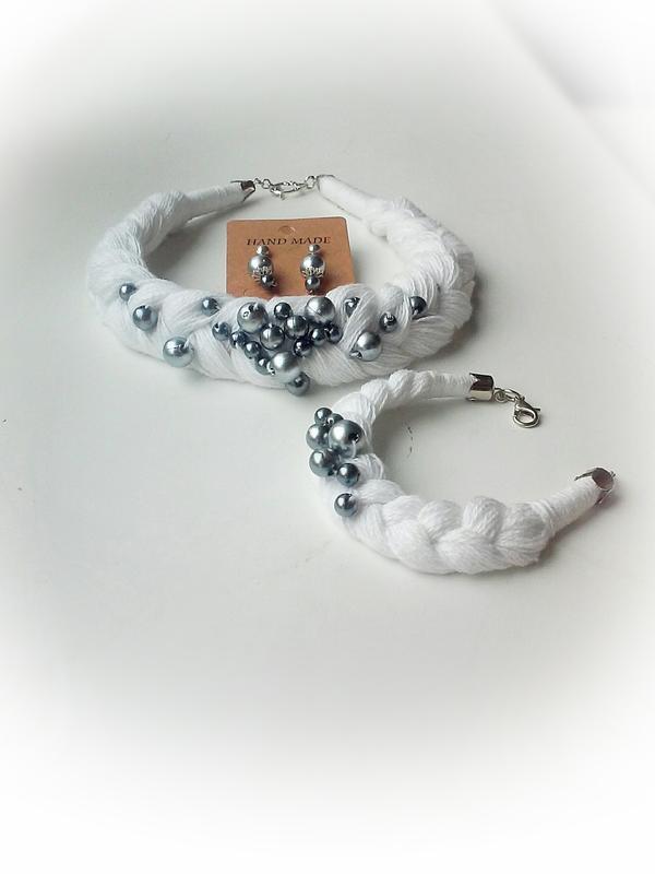 Комплект украшений: колье-коса, браслет и серьги белого цвета с бусинами.