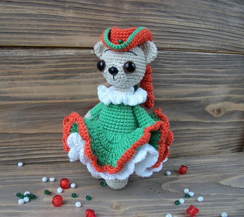 вязаный мишка крючком в оранжевой шляпе и пышном зелёном платье