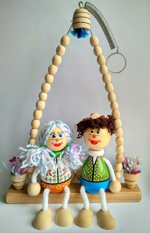 Дерев'яні ляльки на гойдалках